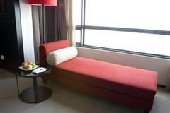 Rotes Sofa durch ein Fenster lizenzfreies stockbild