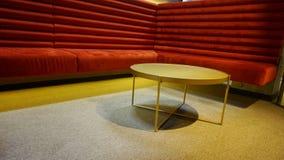 Rotes Sofa für Rest und eine Tabelle in einem Café oder in einem Verein lizenzfreie stockbilder