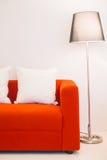 Rotes Sofa mit Kissen- und Lichtlampe Stockfotografie