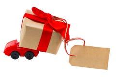 Rotes Spielzeugauto, das Geschenkkasten mit Tag mit leerem Raum für liefert Stockfotografie
