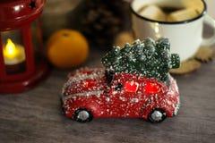 Rotes Spielzeugauto mit Weihnachtsbaum im Dach Glücklicher Mann genießt an den Feiertagen in dem Meer stockbilder