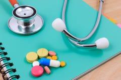 Rotes Stethoskop, Bleistift und viele bunten Pillen, die auf einem dünnen Grünbuch liegen Stockbilder