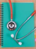 Rotes Stethoskop, das auf einem dünnen Grünbuch liegt Lizenzfreies Stockfoto