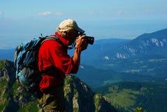 Rotes T-Shirt alter Bergsteiger, der Foto auf die Oberseite eine Klippe nimmt Stockbild