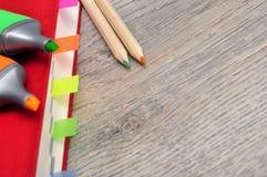 Rotes Tagebuchnotizbuch und farbige Bleistifte, Holz der Markierung auf dem Tisch Stockfotos