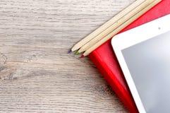 Rotes Tagebuchnotizbuch, weiße Tablette und farbige Bleistifte auf Schreibtisch flehen an Lizenzfreies Stockfoto