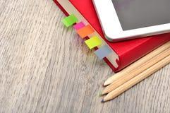 Rotes Tagebuchnotizbuch, weiße Tablette und farbige Bleistifte auf Schreibtisch flehen an Lizenzfreies Stockbild
