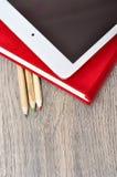 Rotes Tagebuchnotizbuch, weiße Tablette und farbige Bleistifte auf Schreibtisch flehen an Stockbild