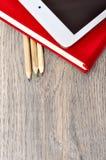 Rotes Tagebuchnotizbuch, weiße Tablette und farbige Bleistifte auf Schreibtisch flehen an Stockfoto