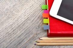 Rotes Tagebuchnotizbuch, weiße Tablette und farbige Bleistifte auf Schreibtisch flehen an Stockfotografie