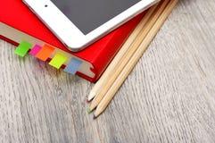 Rotes Tagebuchnotizbuch, weiße Tablette und farbige Bleistifte auf Schreibtisch flehen an Stockbilder