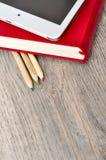 Rotes Tagebuchnotizbuch, weiße Tablette und farbige Bleistifte auf Schreibtisch flehen an Lizenzfreie Stockfotos