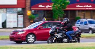 Rotes Taxi und ein Motorrad Stockfotos