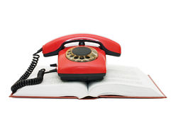 Rotes Telefon auf dem Buch Stockfoto