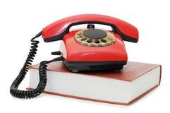 Rotes Telefon auf dem Buch getrennt Stockbilder