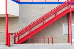 Rotes Treppenhaus gegen Steinwand Stockfotografie