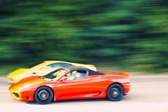 Rotes und gelbes Autoauf Landstraße schnell fahren Lizenzfreies Stockbild