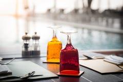 Rotes und gelbes Glas Wasser auf Luxusgedeck Lizenzfreie Stockfotografie