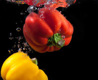 Rotes und gelbes Paprika- und Wasserspritzen. Lizenzfreie Stockfotografie