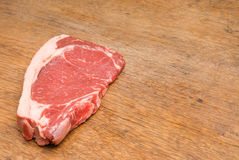 Rotes und geschmackvolles Steak auf einer hölzernen Tabelle Lizenzfreie Stockfotos