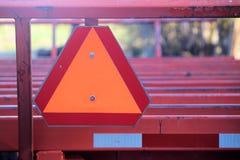Rotes und orange langsames Zeichen auf der Rückseite von roten Hay Wagon Stockbild