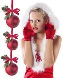 Rotes und reizvolles Weihnachtsmann-Mädchen, das unter Haube sich versteckt Lizenzfreie Stockbilder