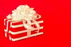 Rotes und weißes gestreiftes Geschenk mit weißen Farbbändern Lizenzfreies Stockbild