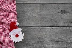 Rotes und weißes kariertes Gewebe mit Sankt-Kopf auf hölzernem Hintergrund Lizenzfreies Stockfoto