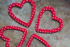 Rotes und weißes punktiertes Herz formte Dekorationen auf hölzernem Hintergrund lizenzfreie stockfotos