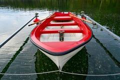 Rotes und weißes Skiff wenig im schwedischen See stockfotografie
