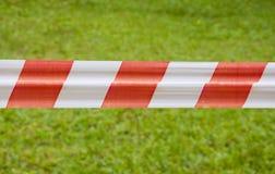 Rotes und weißes warnendes Band auf Hintergrund des grünen Grases Lizenzfreie Stockbilder