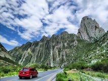 Rotes Van, das durch eine szenische Straße in einem Berggebiet fährt stockfoto
