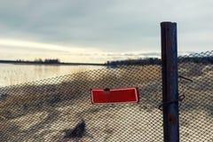 Rotes verbietendes Zeichen auf einem Zaun durch den See Stockfotografie
