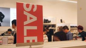 Rotes Verkaufs-Zeichen und Leute-Reihe am Kassierer im Bekleidungsgeschäft Große Weihnachtsfreigaben-Förderung im Einkaufszentrum stock footage