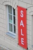 Rotes Verkaufszeichen außerhalb des Fensters Stockbild