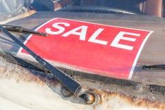 Rotes Verkaufszeichen auf grungy und alter Gebrauchtwagenwindschutzscheibe, Automobil Stockbild