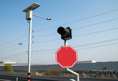 Rotes Verkehrszeichen mit der Ampel nahe durch eine Solarlampe Stockfoto