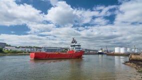 Rotes Versorgungsschiff-nähernder Hafen Stockfoto