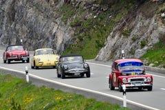 Rotes Volvo PV544, ein dunkelgrünes Daimler SP250, gelbes Porsche 356 und eine rote Alpha-Romeo Giulia-Spinne Stockfotografie