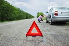 Rotes Warndreieck mit einem aufgegliederten Auto Zusammenbruch des Autos im schlechten Wetter stockfotos
