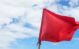 Rotes warnendes fahnenschwenkendes auf dem blauen Himmel Lizenzfreies Stockfoto