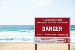 Rotes Warnschild auf einem Ozeanstrand mit Wellen auf dem Hintergrund Stockbilder