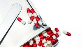 Rotes, weißes Antibiotikum kapselt Pillen mit Schatten auf Edelstahldrogenbehälter ein Stockfotos