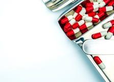Rotes, weißes Antibiotikum kapselt Pillen mit Schatten auf Edelstahldrogenbehälter ein Lizenzfreie Stockbilder