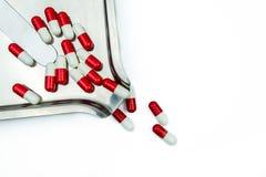 Rotes, weißes Antibiotikum kapselt Pillen mit Schatten auf Edelstahldrogenbehälter ein Lizenzfreies Stockfoto