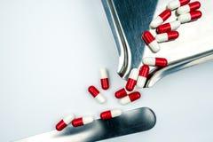 Rotes, weißes Antibiotikum kapselt Pillen mit Schatten auf Edelstahldrogenbehälter ein Stockfotografie