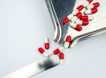 Rotes, weißes Antibiotikum kapselt Pillen mit Schatten auf Edelstahldrogenbehälter ein Lizenzfreie Stockfotografie