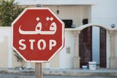 Rotes weißes zweisprachiges Anglo arabisches achteckiges Stoppschild Stockfoto