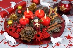 Rotes Weihnachten verzierte Kranzplatte mit vier brennenden Kerzen auf einer Tischdecke, die mit wei?en Schafen umgeben wurde stockfotos