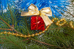 Rotes Weihnachtsgeschenk mit einem Bogen unter dem Weihnachtsbaum Lizenzfreies Stockfoto